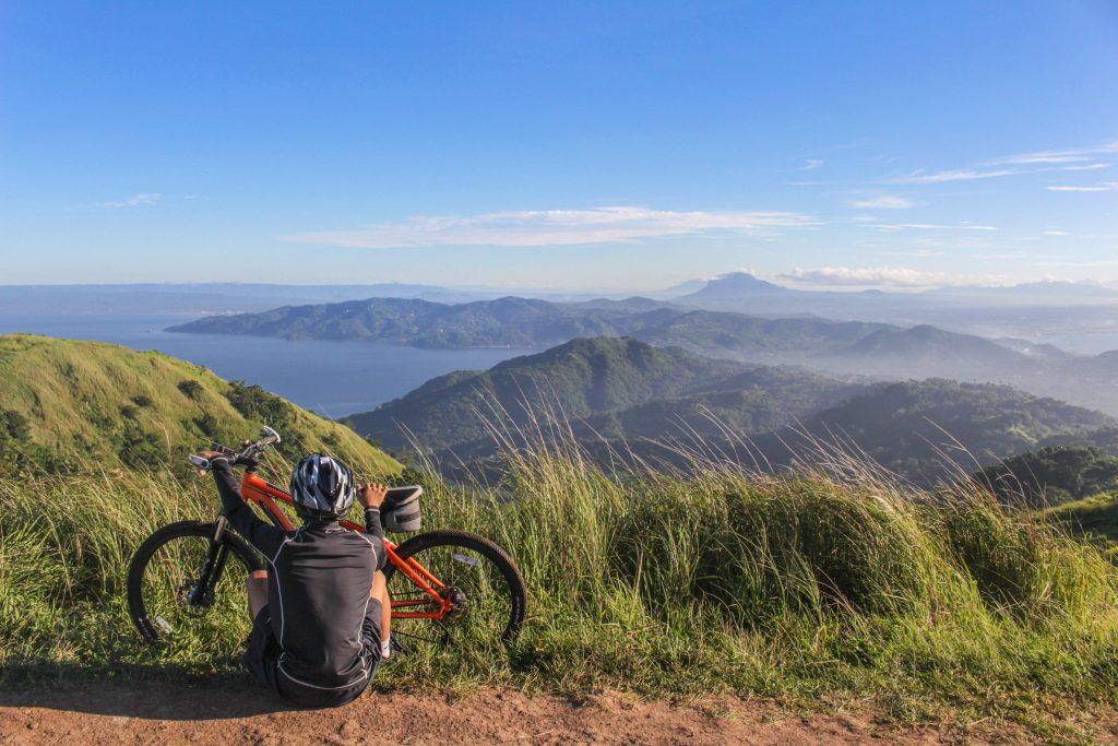 met de fiets op reis - fietsroute in Europa - fietser met fiets in de bergen geniet van het uitzicht